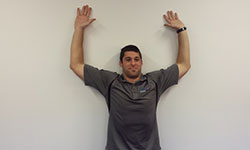 Photo: End the squat at the starting position: with the elbows and hands flat on the wall at a 90 degree angle.