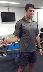 Photo: Cable pulley machine set at the level of the elbow. Arm turned away from the body