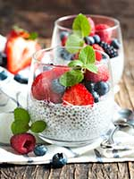 Photo: Chia pudding in a clear glass topped with strawberries, blueberries, raspberries, and mint.