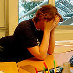 Photo: Woman with head in her hands at her desk.